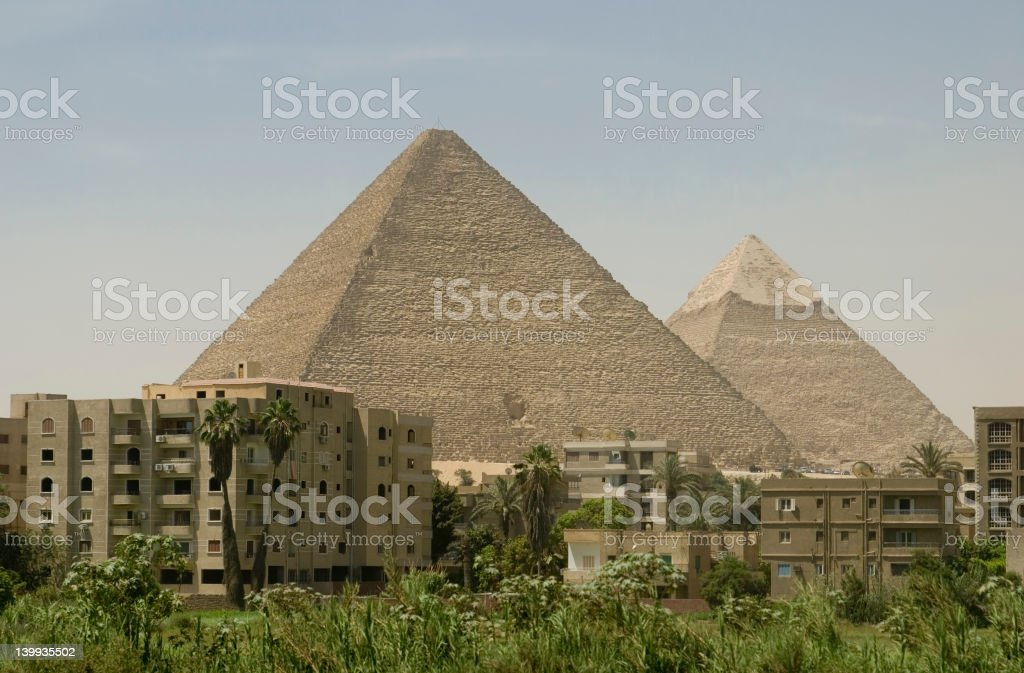 The Pyramids in Giza behind urban buildings royalty-free stock photo