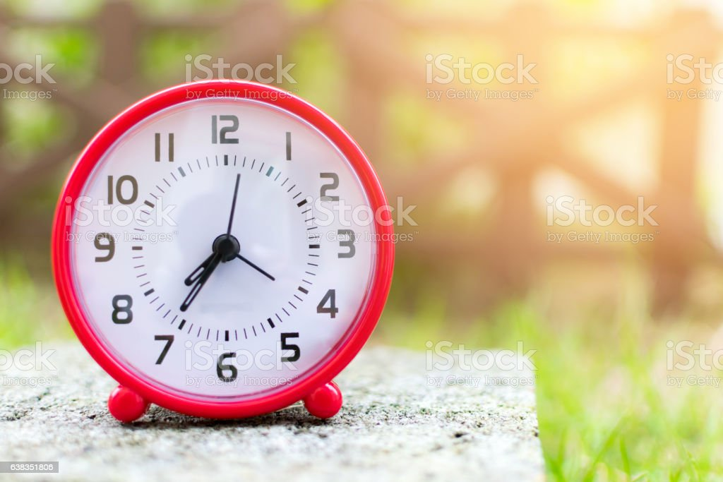 The red clock holding on the floor in the garden. stock photo