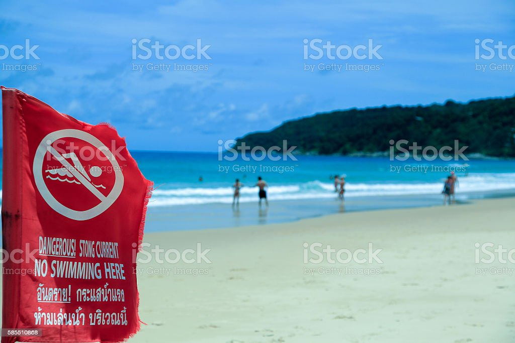 The red flag prohibiting swimming. A sea shore. Of the stock photo
