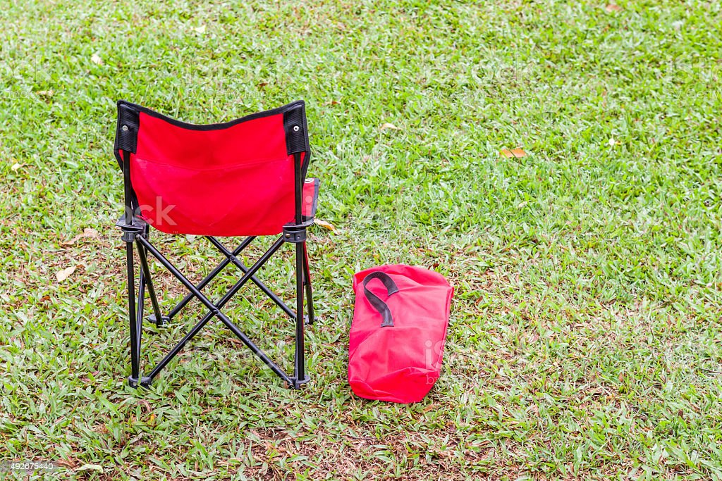 The red folding chair and the cover on green grass. stock photo