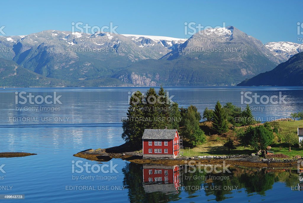 The red, Norwegian house in a blue fjord stock photo
