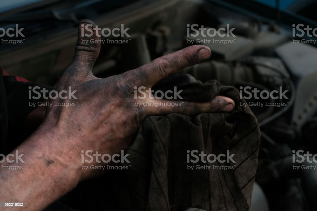 The repairman of cars wipes hands a rag stock photo