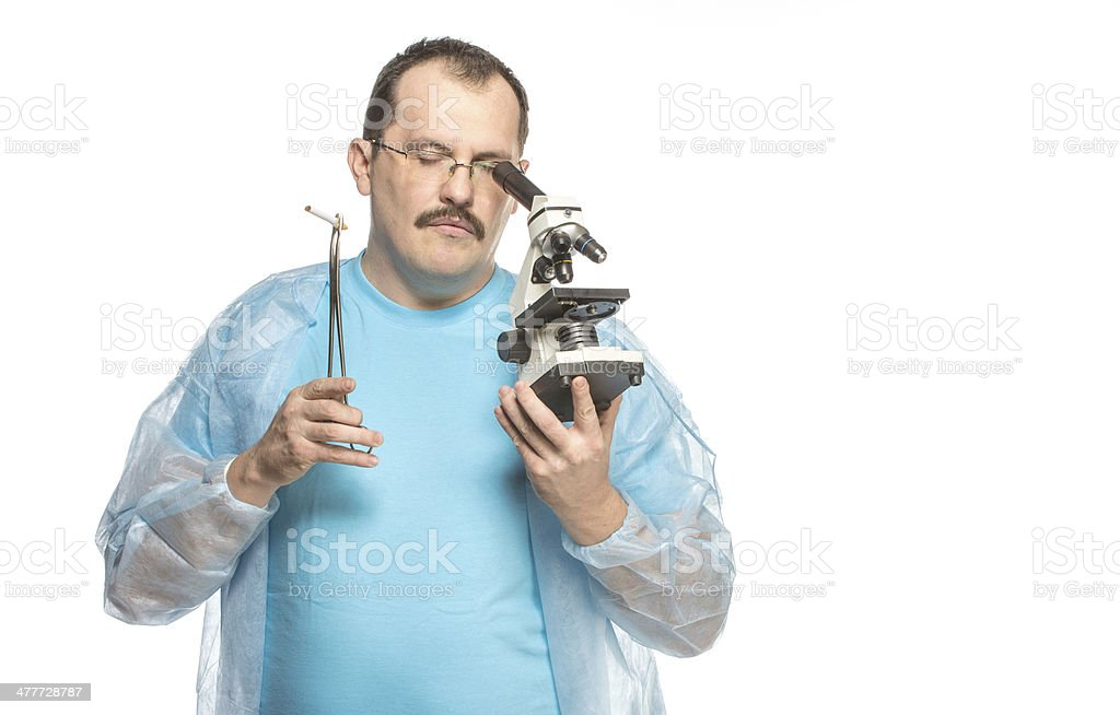 The ridiculous fat surgeon with cigarette and microscope stock photo