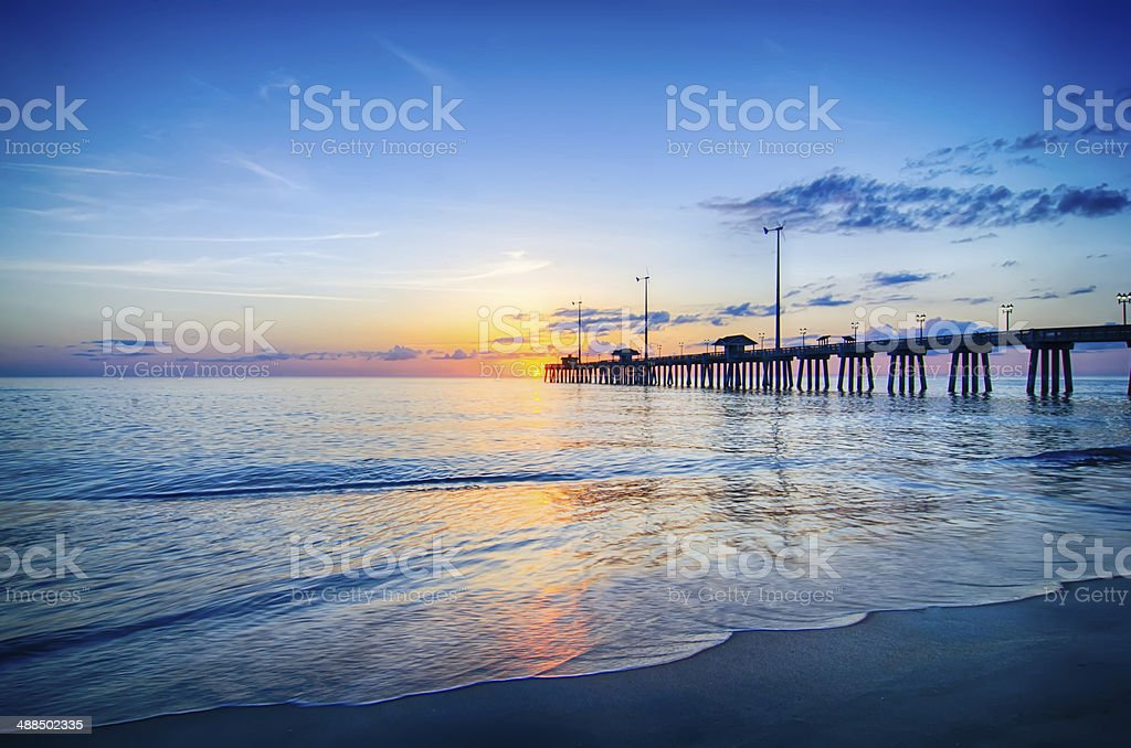 The rising sun peeks through clouds and is reflected stock photo
