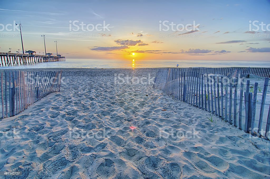 The rising sun peeks through clouds stock photo