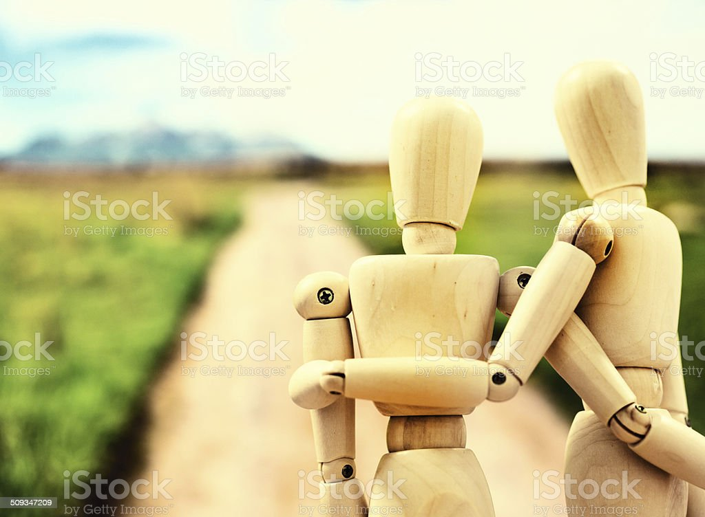 The road ahead. Two puppets set off, arm in arm stock photo