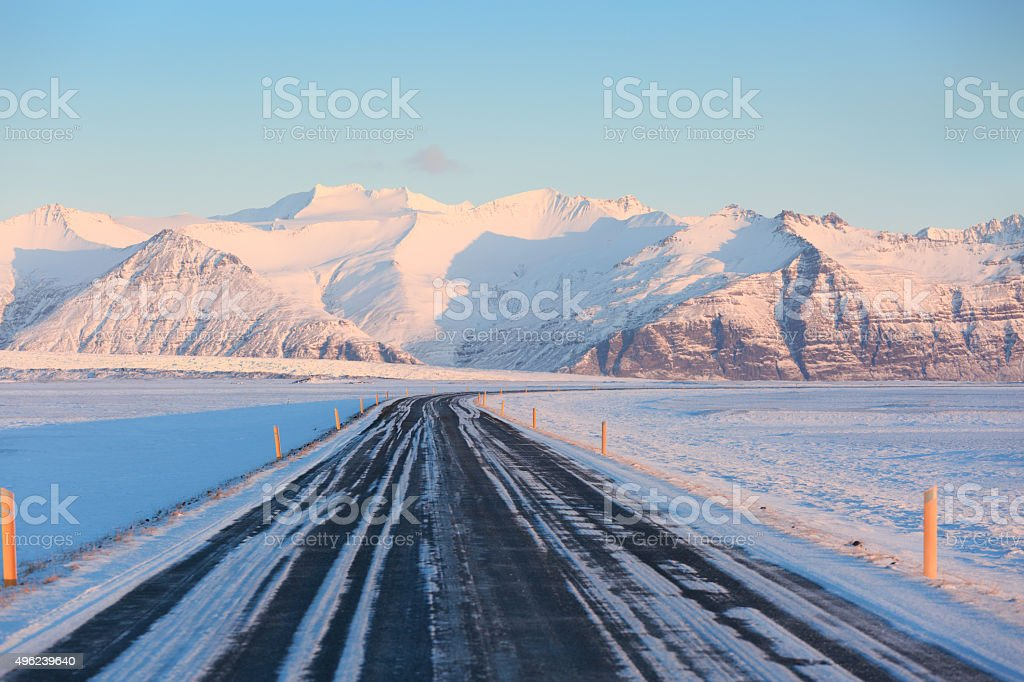 The road on a sunny day to the snow-capped mountains. stock photo