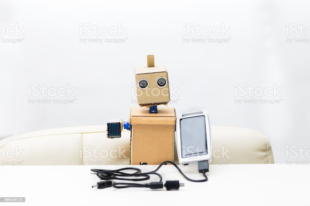 The robot holds a small and large solar battery stock photo