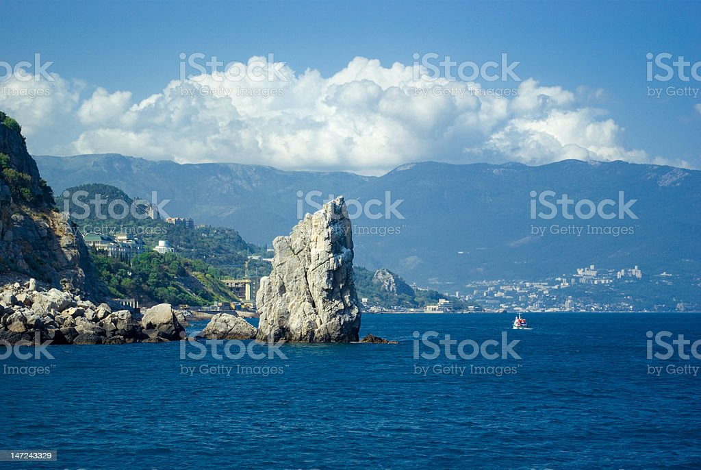 The rock called 'sail' with a boat near Yalta royalty-free stock photo