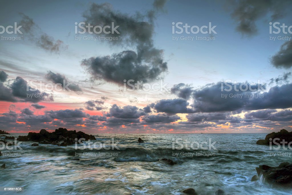 the rocks on the seashore at moody sunrise stock photo
