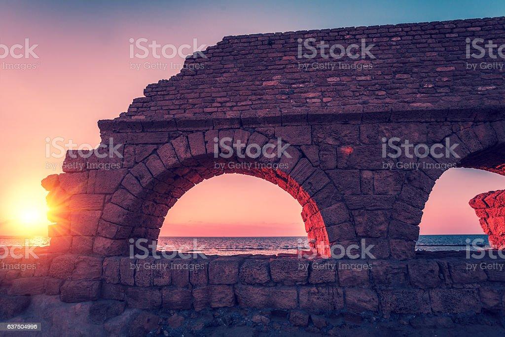 the Roman aqueduct in ancient city Caesarea at sunset stock photo