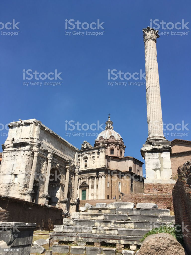 The Roman Forum  Septimius Severus Arch and the Column of Phocus with Chiesa dei Santi Luca e Martina in the background.  Blue, cloudless sky on a hot summer's day in Rome. stock photo
