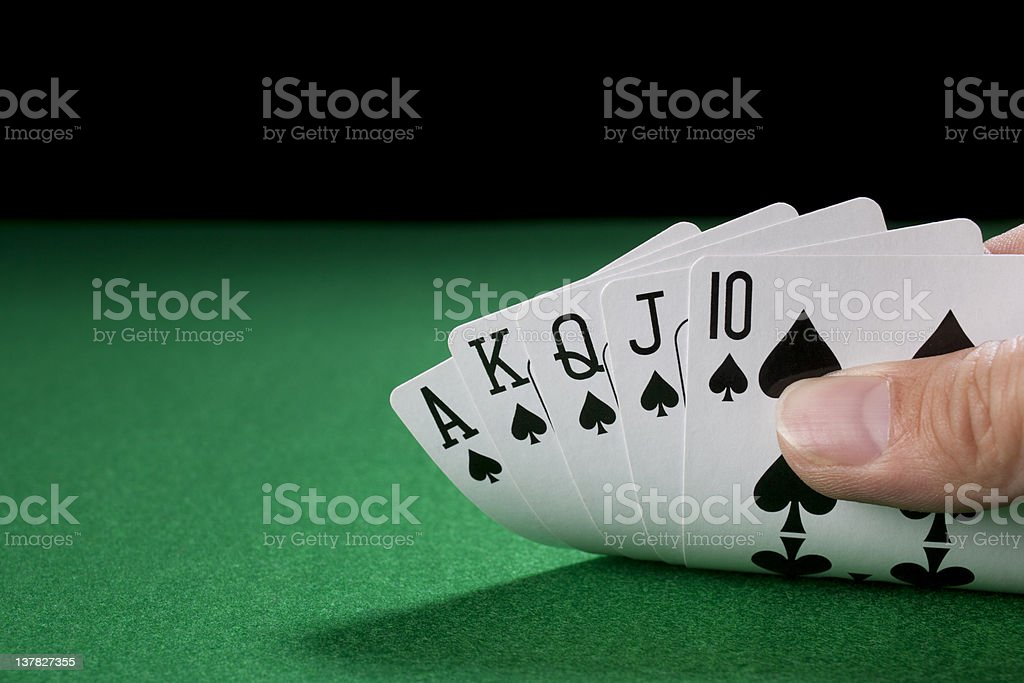 The Royal Flush in hand on a green poker table stock photo
