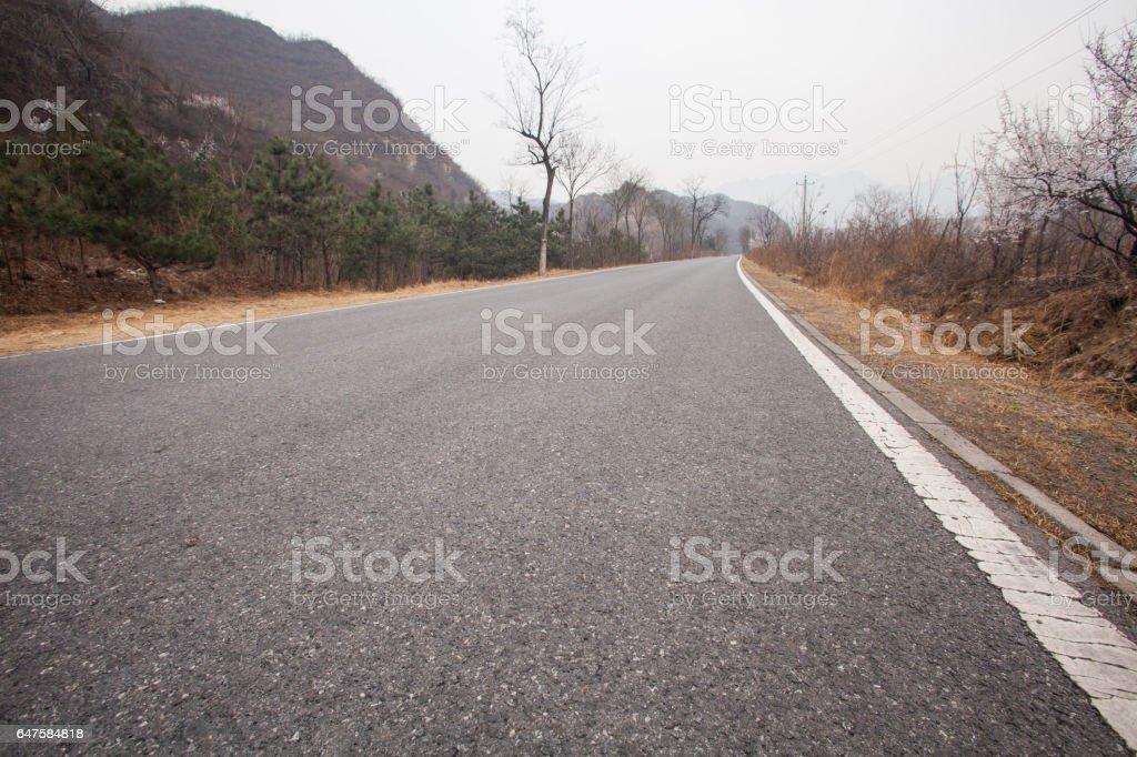 The rugged mountain road is shrouded in haze in Beijing, China stock photo