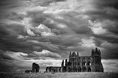 The ruins of Whitby Abbey with dramatic cloudy backdrop.