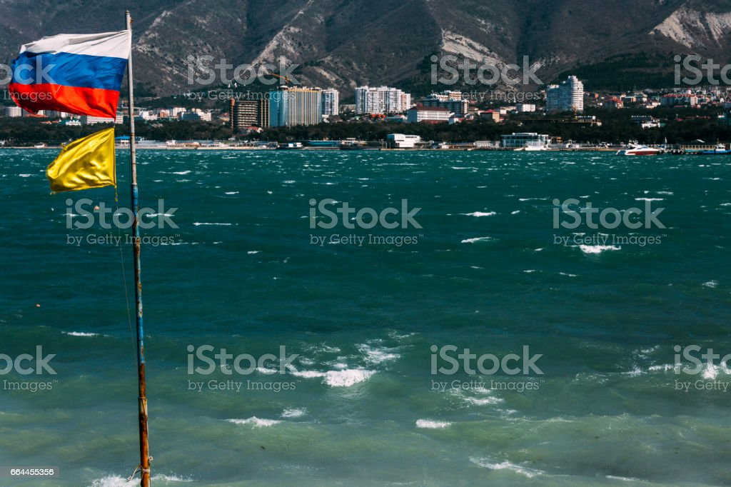 The Russian flag is flying on the flagpole against the backdrop of the Black Sea coast of Gelendzhik Bay. Gelendzhik, Russia stock photo