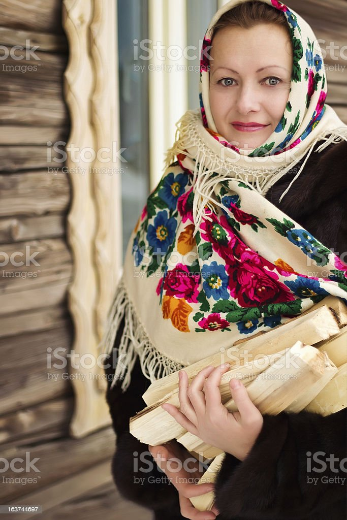 The Russian woman carries firewood royalty-free stock photo