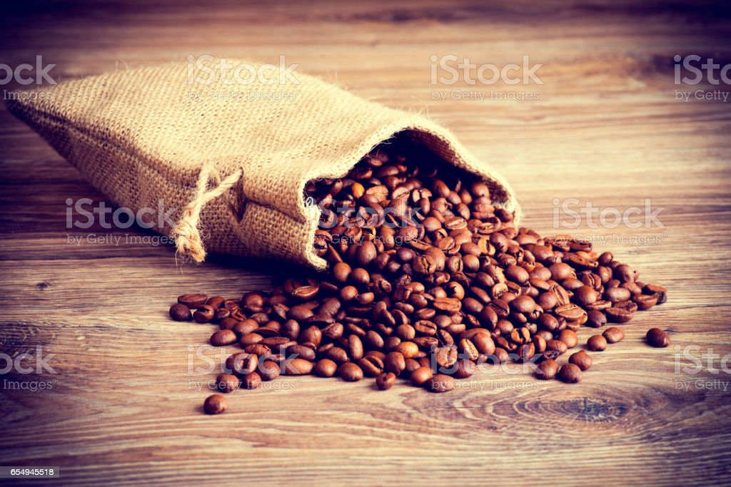 The sack of coffee beans on wooden background. stock photo