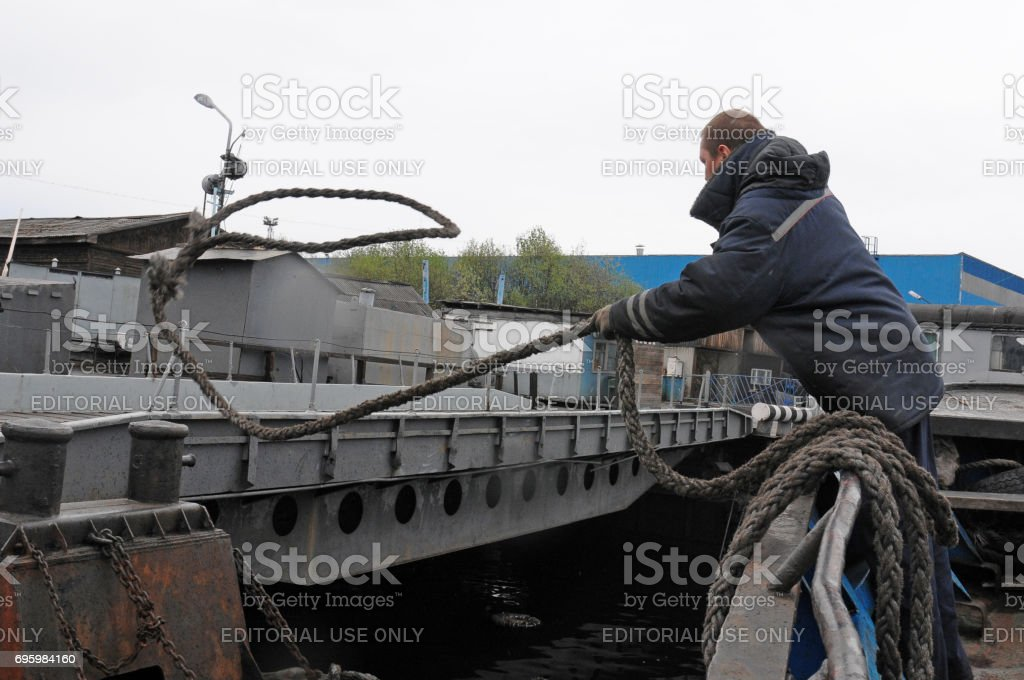 The sailor throws the mooring end from the ship's side onto the bollard stock photo