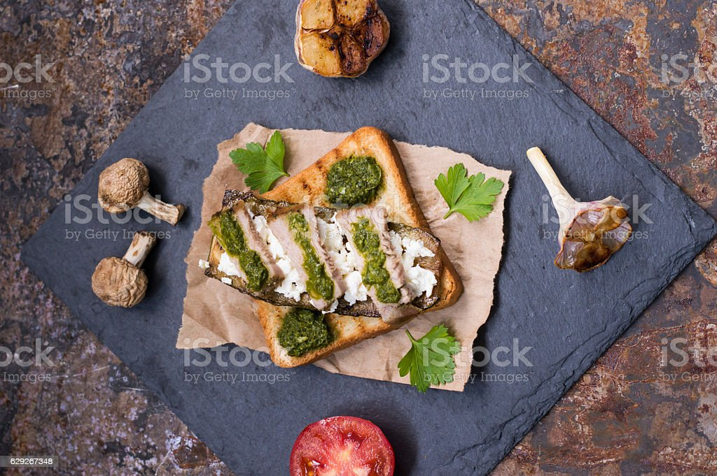 The sandwich of toast, cheese, mushrooms, grilled meat, zucchini and stock photo
