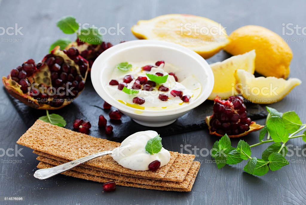 The sauce (dip) of yogurt with pomegranate and mint stock photo