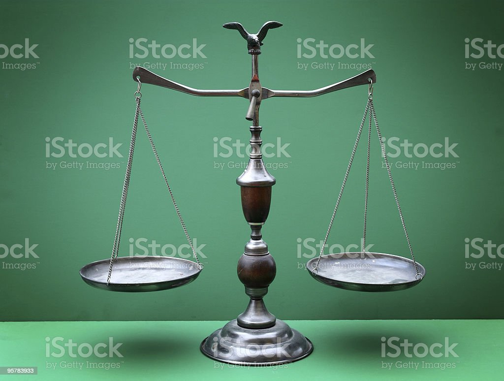 The scales of justice against a green background stock photo