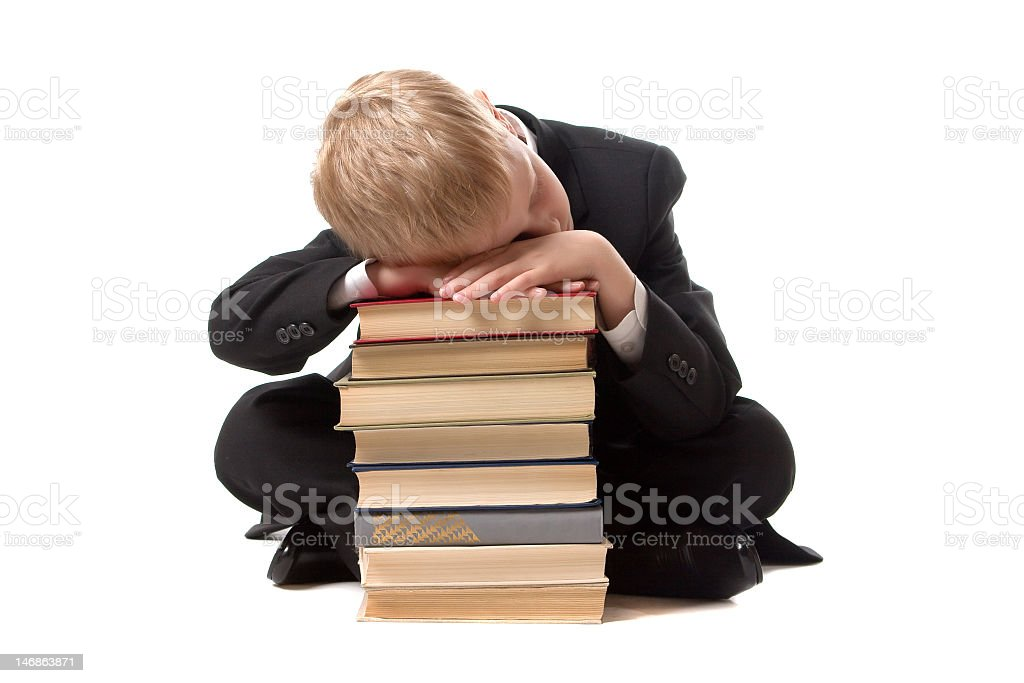 The schoolboy has fallen asleep on a pile of books. royalty-free stock photo