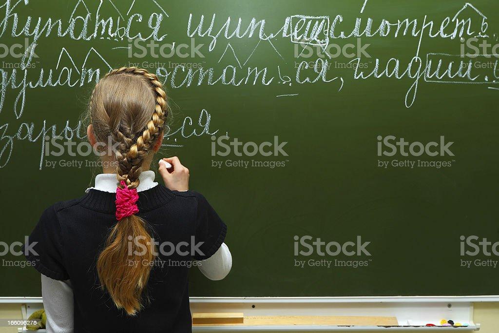 The schoolgirl writes chalk on a blackboard royalty-free stock photo
