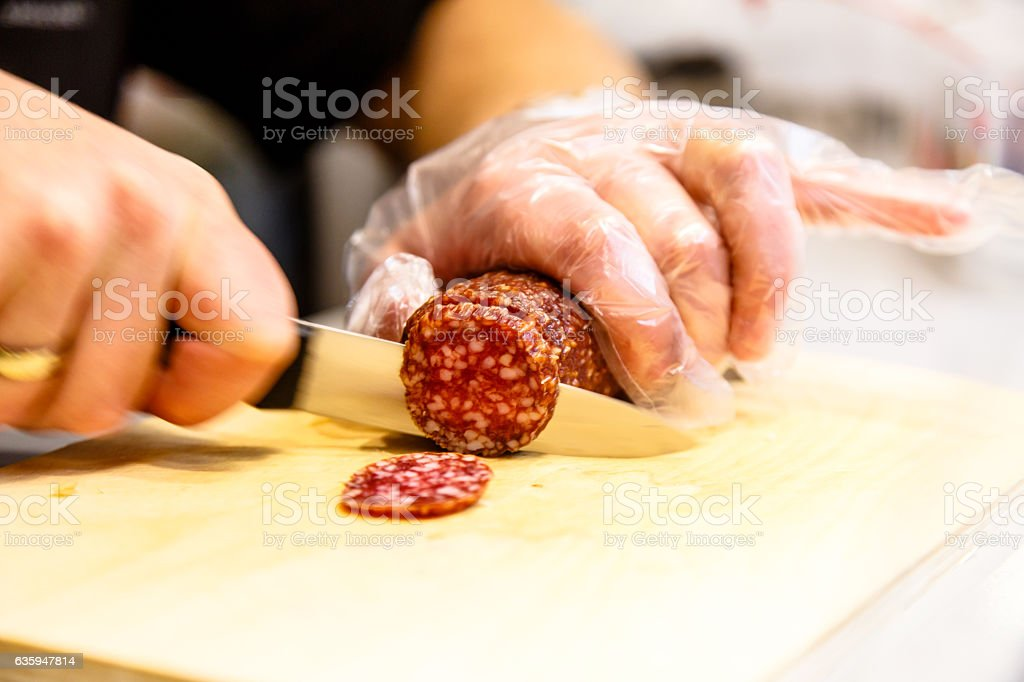 The seller is cutting a sausage stock photo