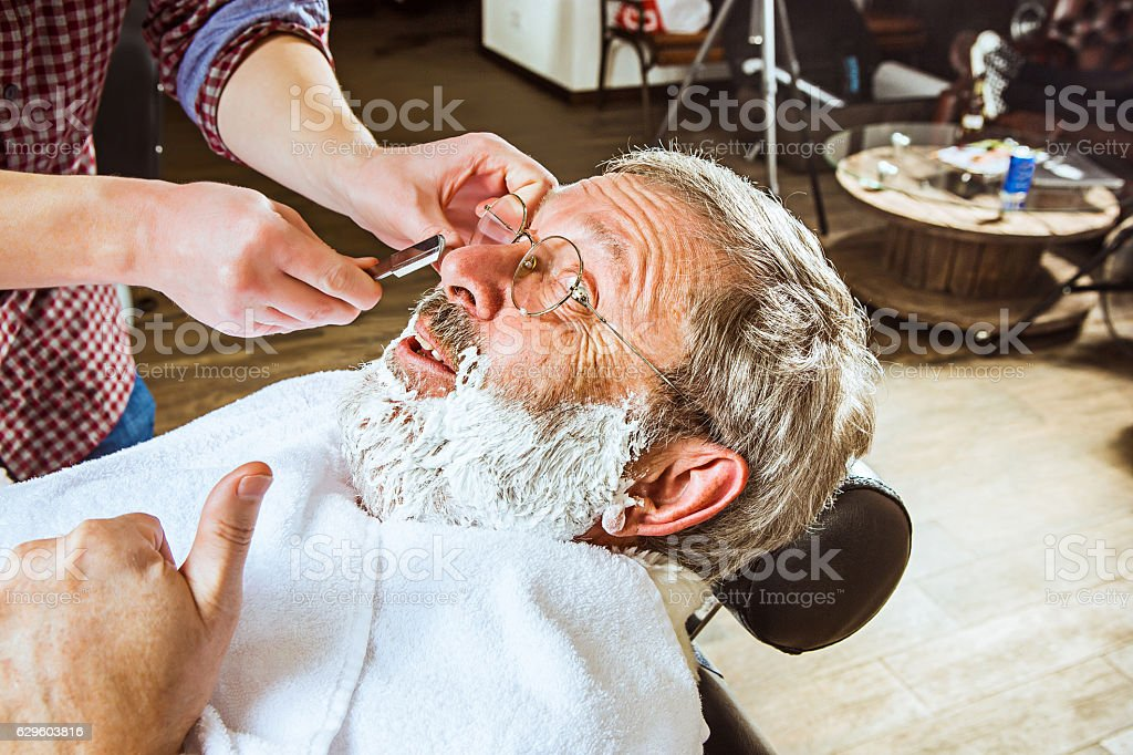 The senior man visiting hairstylist in barber shop. stock photo