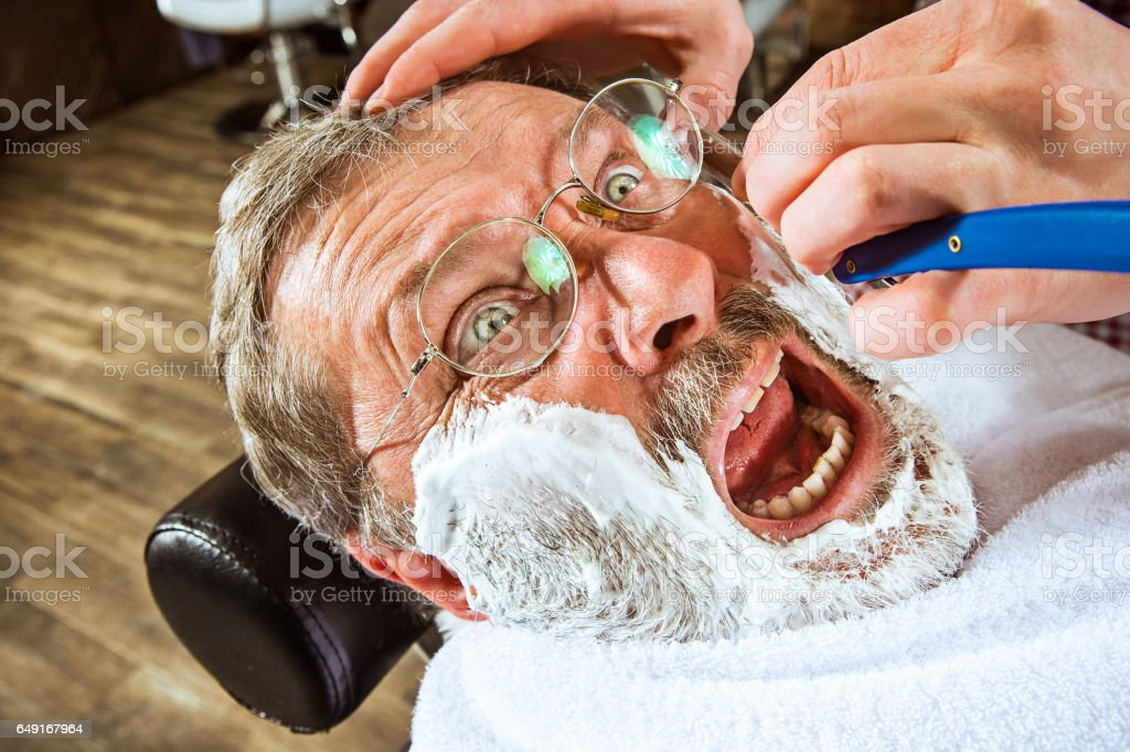 The senior man visiting hairstylist in barber shop stock photo