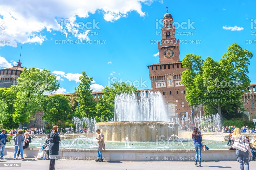 The Sforzesco Castle main tower behind the fountain with traveler and blue sky background in Milan, Italy. stock photo
