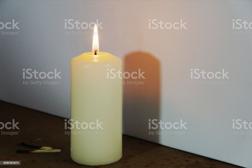 The shadow of a burning candle. stock photo
