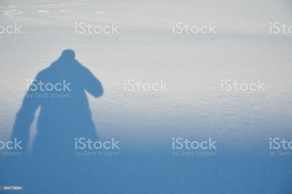 The shadow of a man on white snow stock photo