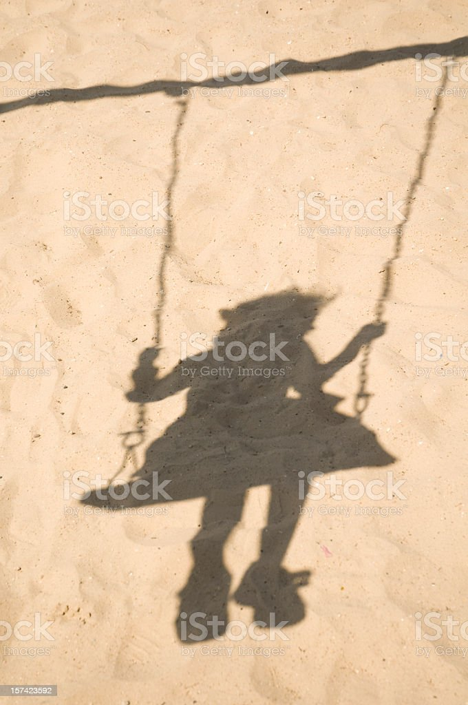 The shadow of a young girl swinging cast upon the sand  stock photo