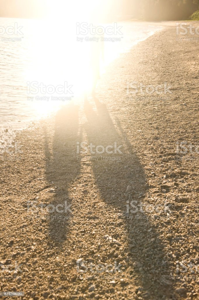 The shadow of the couple standing on the beach in the evening stock photo