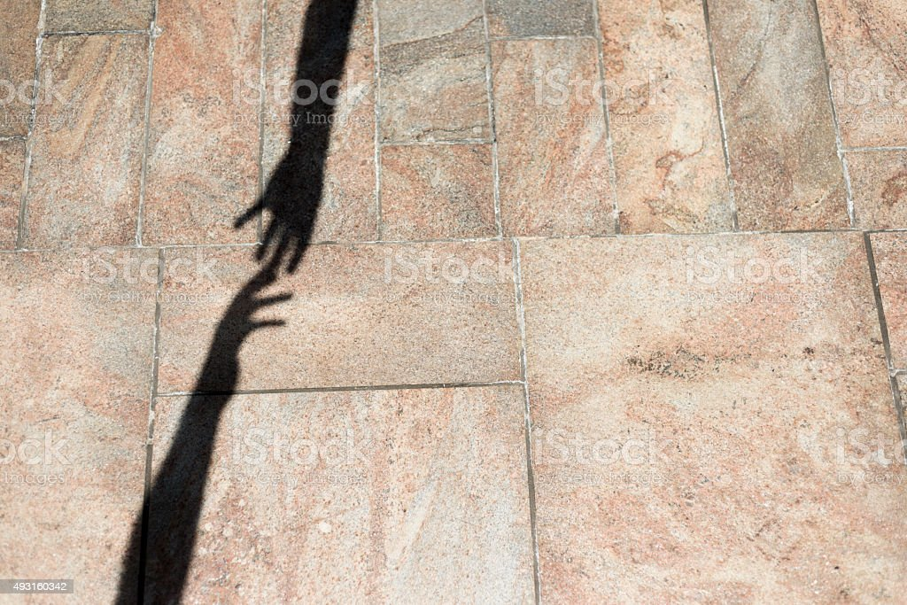 The shadow of two Hands touching in the Air stock photo