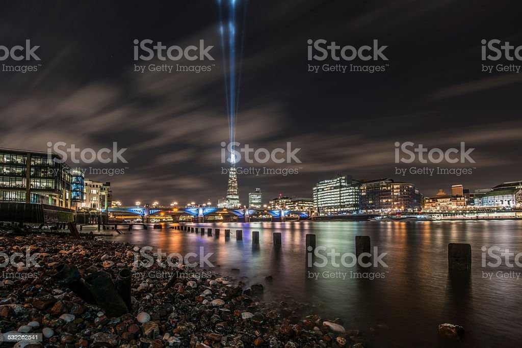 The Shard tower shining rays of light during the night stock photo