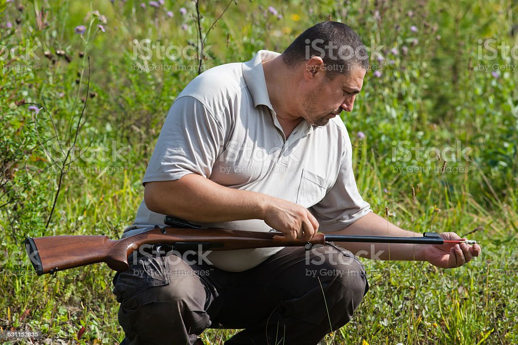 the shooter cleans the barrel of rifle stock photo
