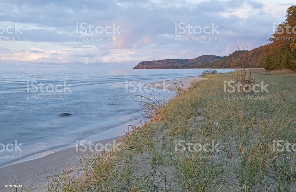 The shoreline of water with sand and grass at dusk royalty-free stock photo