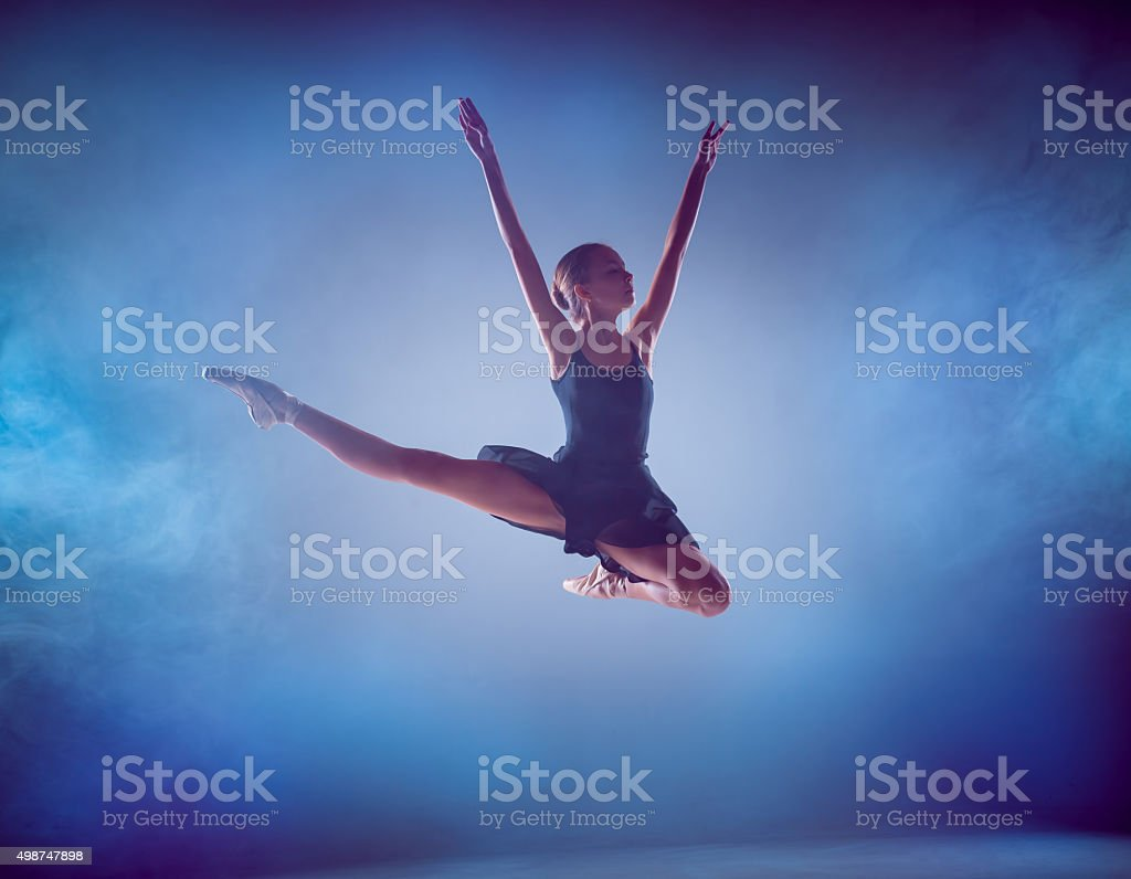 The silhouette of young ballet dancer jumping on a blue stock photo
