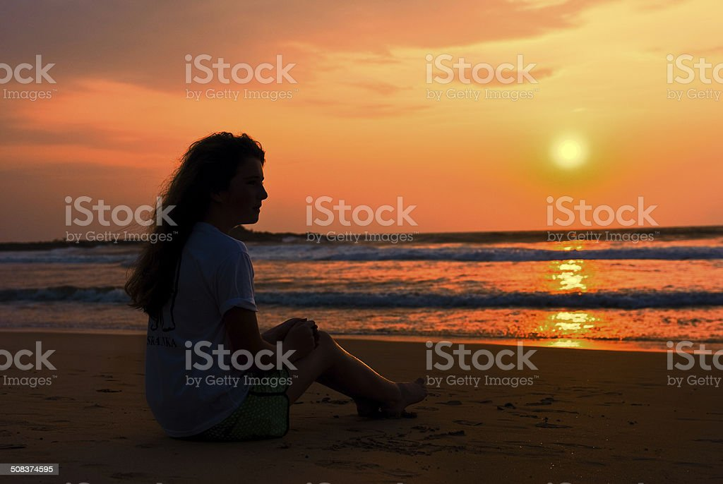 The silhouette ot girl sits on the beach stock photo