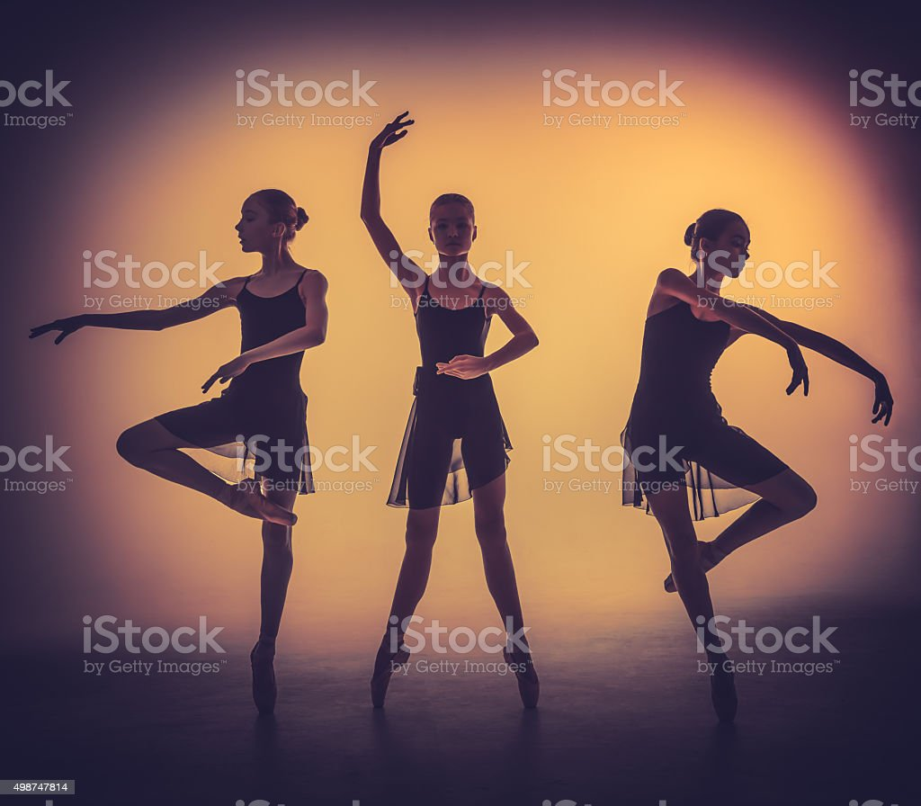 The silhouettes of young ballet dancers posing on a gray stock photo