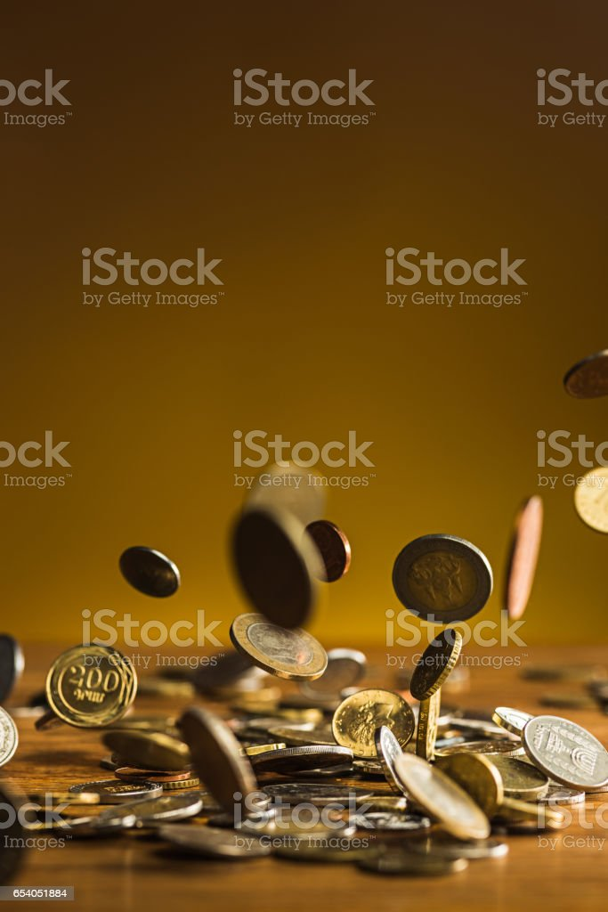 The silver and golden coins and falling coins on wooden background stock photo