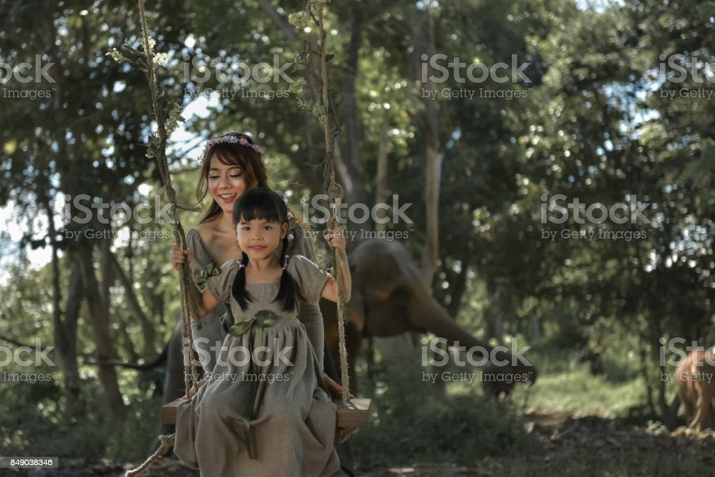 The sister is swinging to her sister under the shady trees in the tropical forest. She is happy and fun stock photo