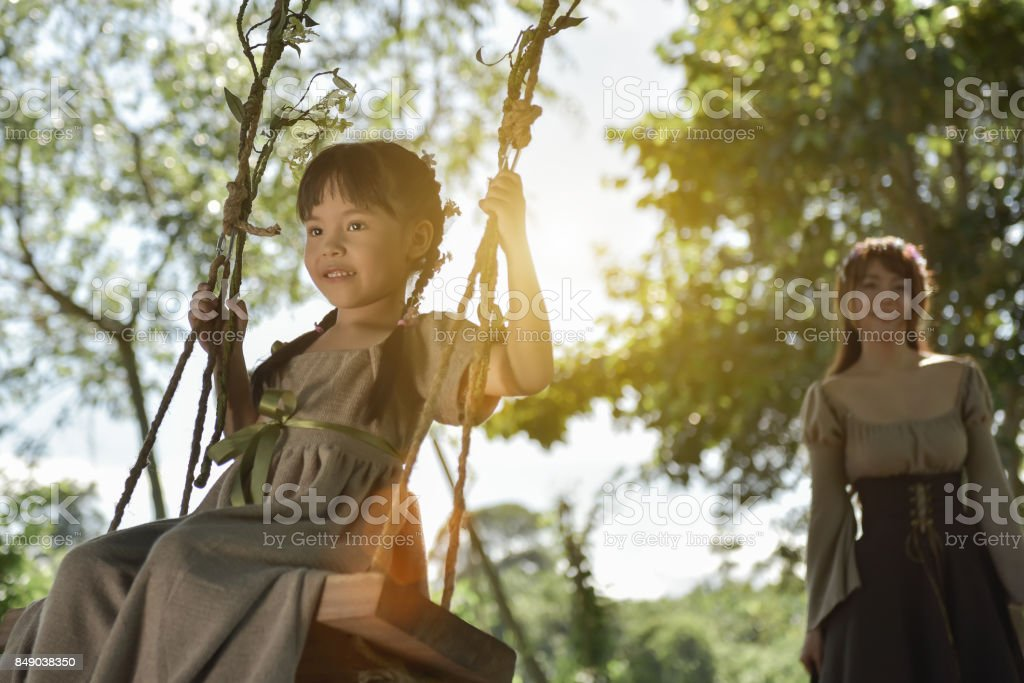 The sister is swinging to her sister under the shady trees in the tropical forest. stock photo