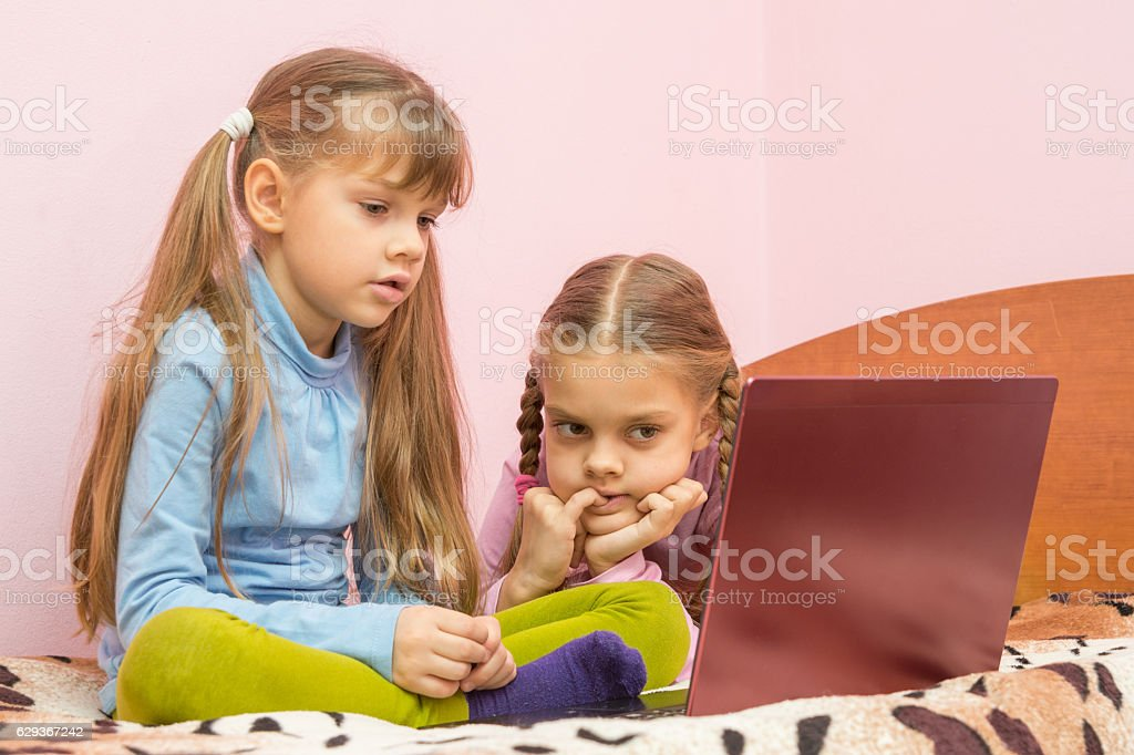 The sisters are interested in watching a laptop screen stock photo