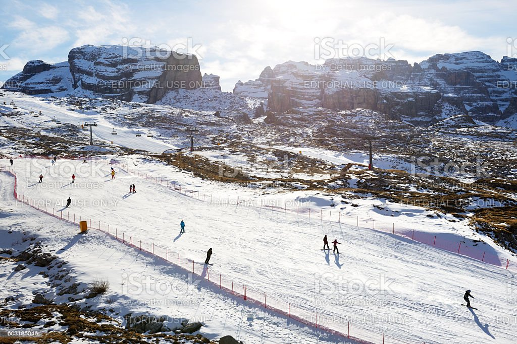 The ski slope and skiers at Passo Groste area. stock photo