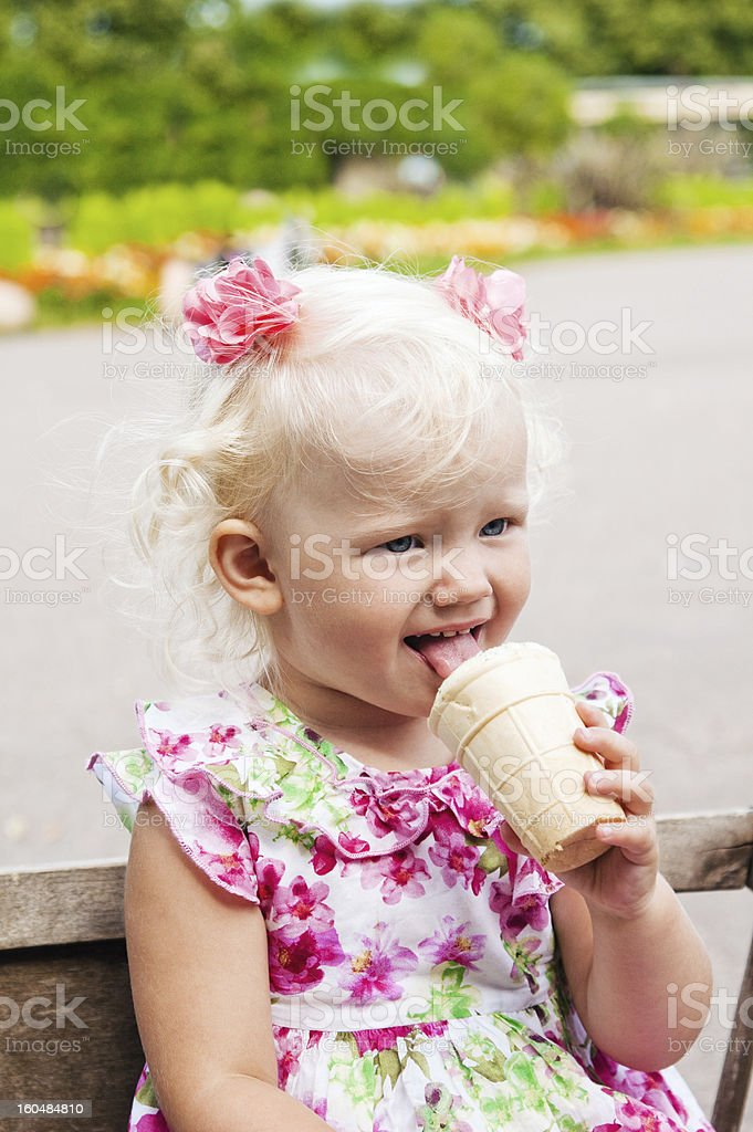 The small blond girl eats ice-cream in a summer garden royalty-free stock photo