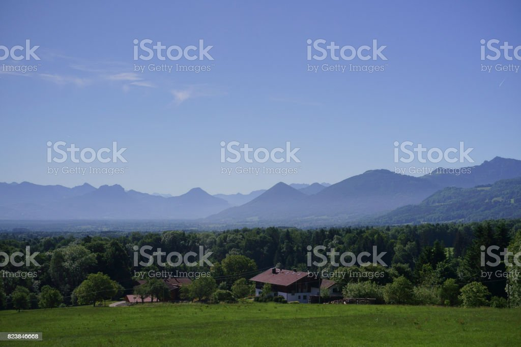 The small cottage hut in the green valley surrounded with wood stock photo